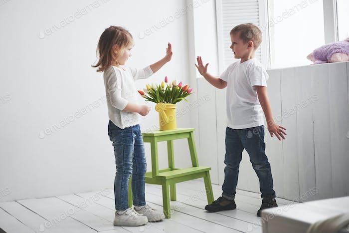 Schöner Junge und Mädchen mit Tulpen. Muttertag, 8. März, Happy Birthday