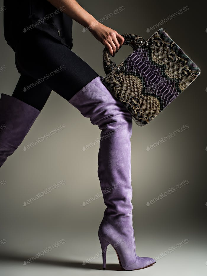 Beautiful woman in purple high boots. Fashionable girl holds sty