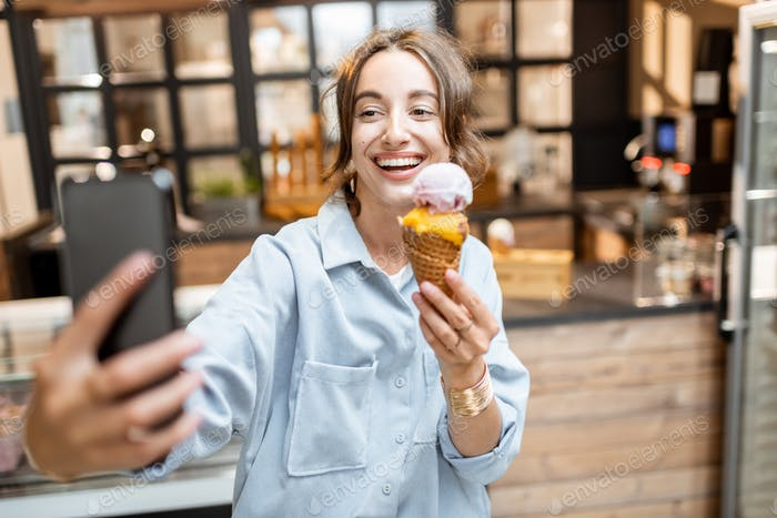 Cheerful woman with ice cream in the shop