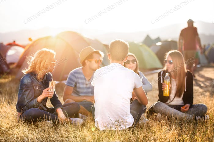 Teenagers sitting on the ground in front of tents, eating
