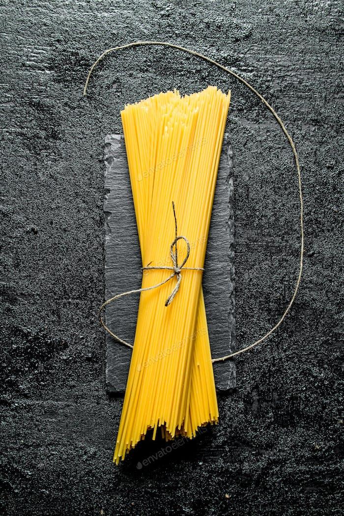 Dry pasta spaghetti on a stone Board.