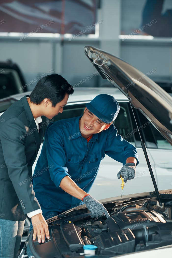 Car owner and mechanic at workshop