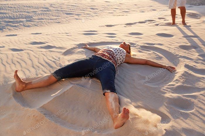 Mujer mayor acostada en Playa haciendo Arena ángel en vacaciones