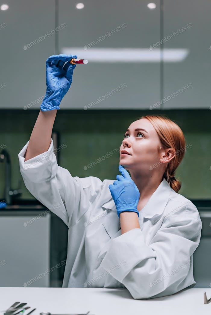 Female medical or scientific researcher looking at a test tube in a laboratory