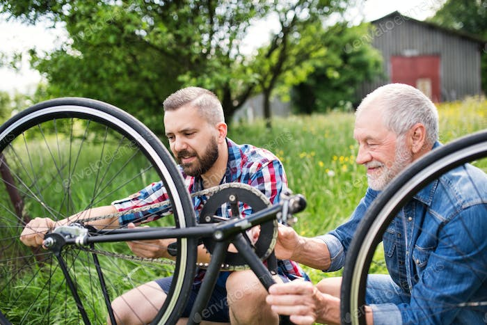 An adult hipster son and senior father repairing bicycle outside on a sunny day.