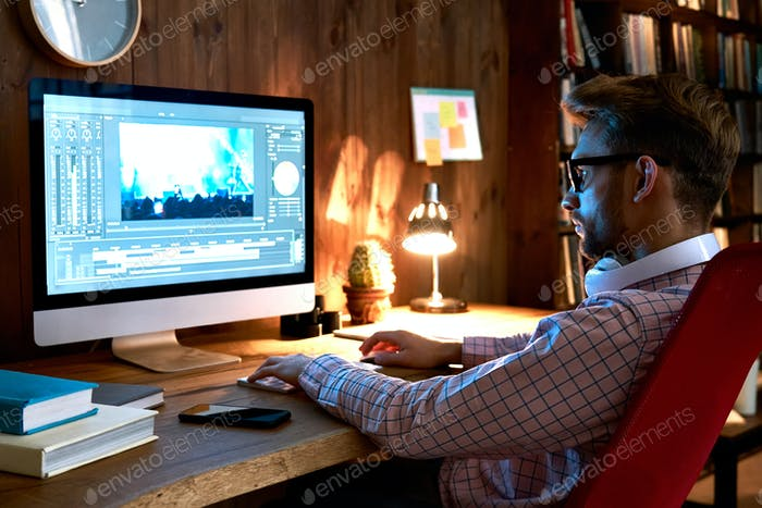 Male videographer using computer editing video footage visual content.