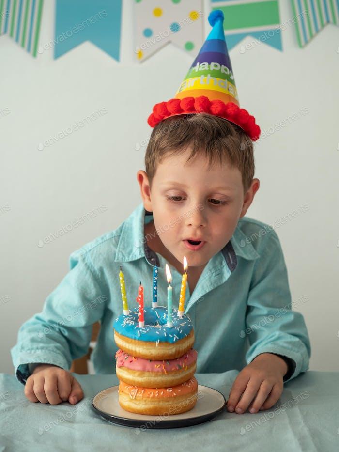 Kind bläst die Kerze auf Geburtstagskuchen aus
