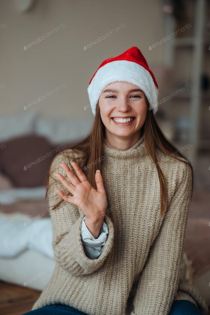Portrait of friendly brunette woman in santa hat waving raised hand