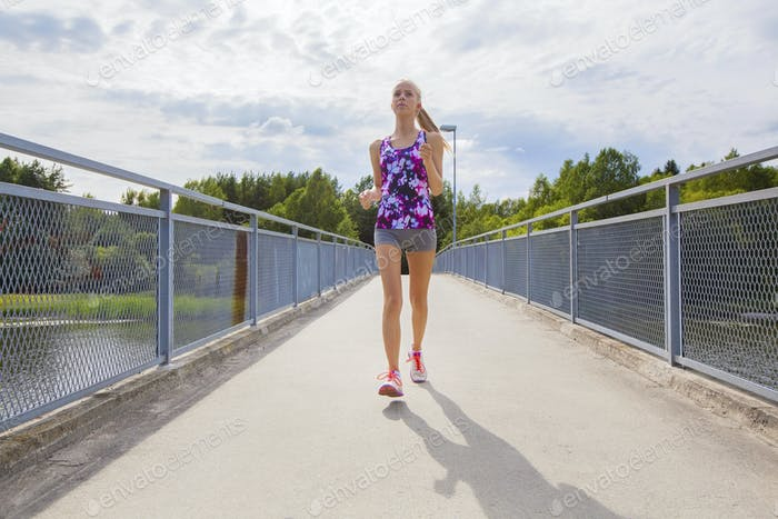 Focused young woman running on bridge over a lake