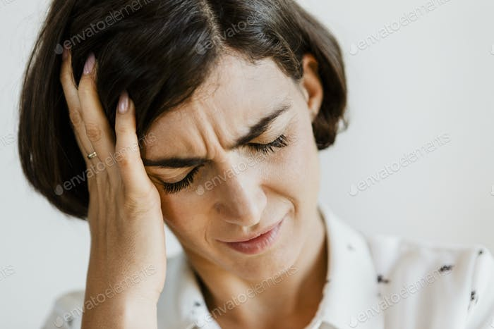 Unhappy woman holding her forehead