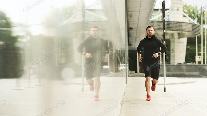 Handsome athlete jogging near urban building with mirror windows