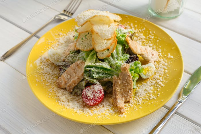 Restaurant food closeup. Caesar chicken salad with parmesan