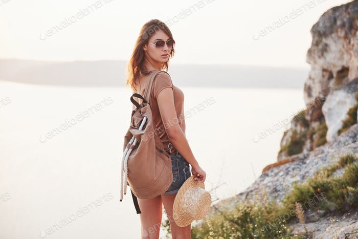 Young tourist woman on the top of the mounting and looking at a beautiful bay landscape. Hiking