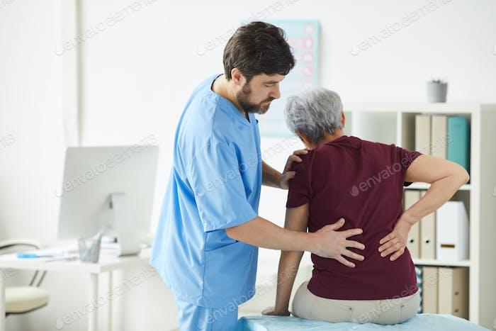 Arzt untersucht den Rücken des Patienten