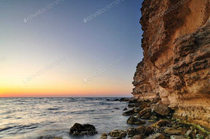 Beautiful pink sunset, rock and water stones with green moss landscape