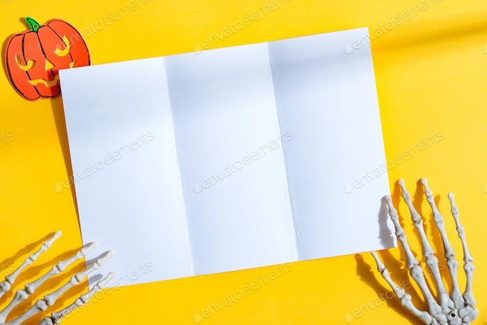 Trifold mock-up paper brochure in a skeleton's hands