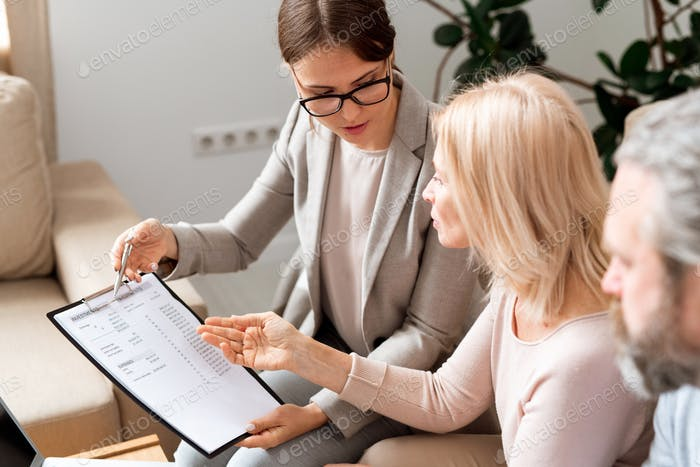 Young and mature women discussing financial expenses while negotiating
