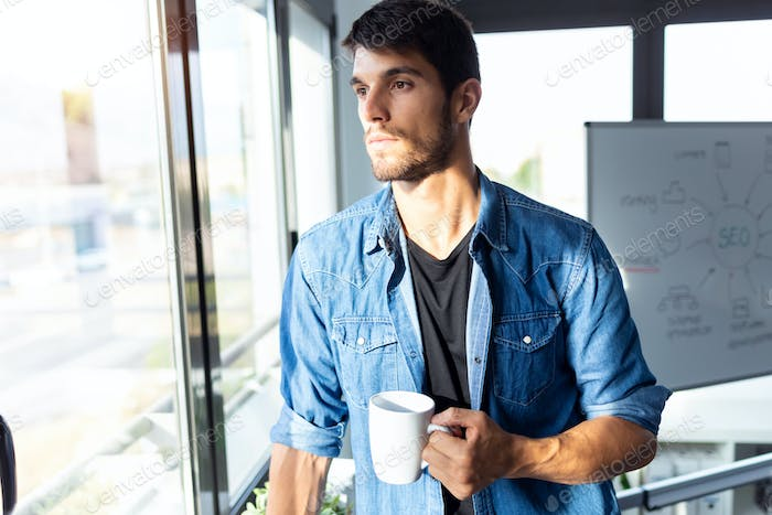 Pensive young businessman looking through the window while drinking coffee