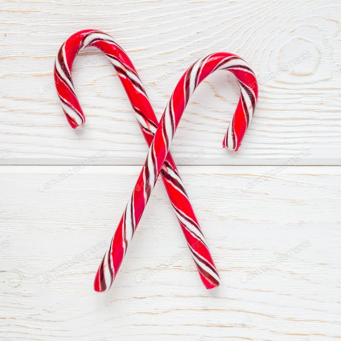 Crossed peppermint candy canes on white wooden background, top view, square