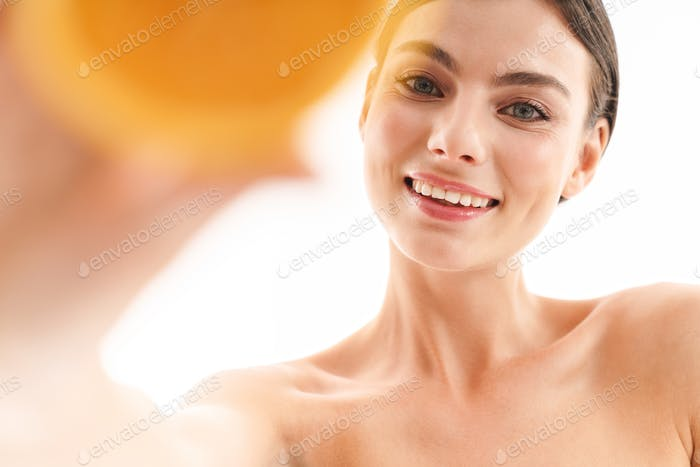 Beauty portrait of an attractive smiling young topless brunette woman