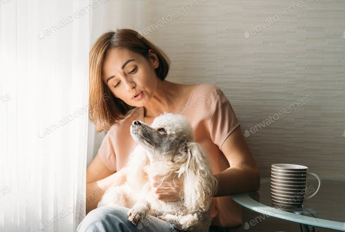 Single young brunette woman with poodle dog on hands sitting by window at