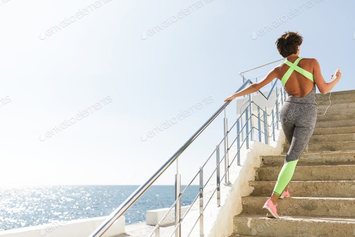 Pretty woman from back in modern gray sport suit getting up by stairs with beautiful sea view