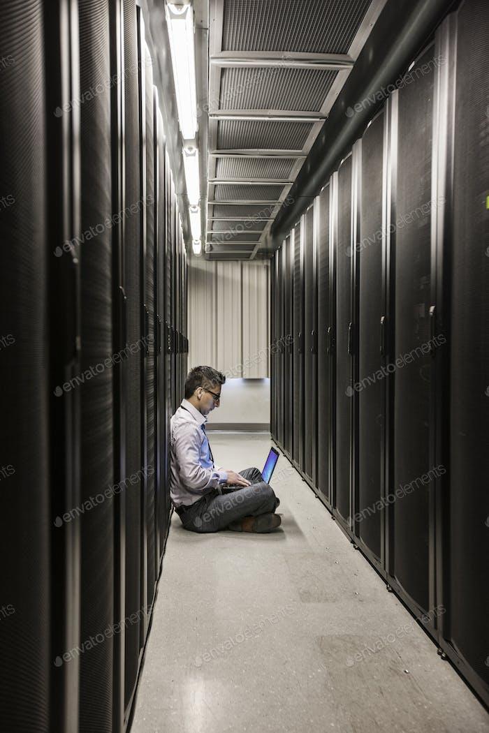 Hispanischer Techniker führt Diagnosetests auf Computerservern in einer großen Serverfarm.