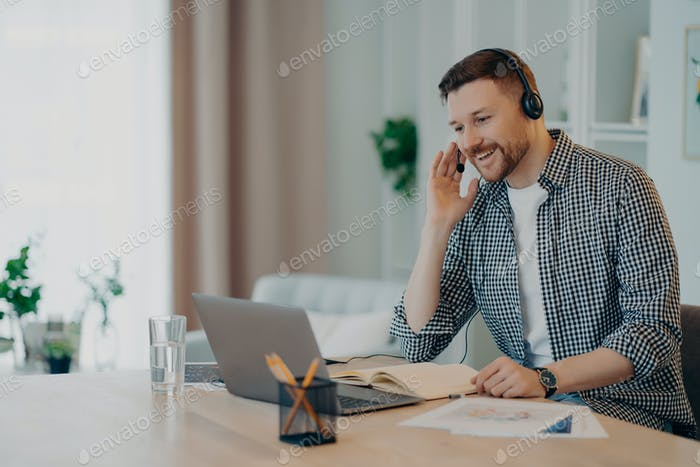Man participates in self improvement webinar wears checkered shirt communicates by video call