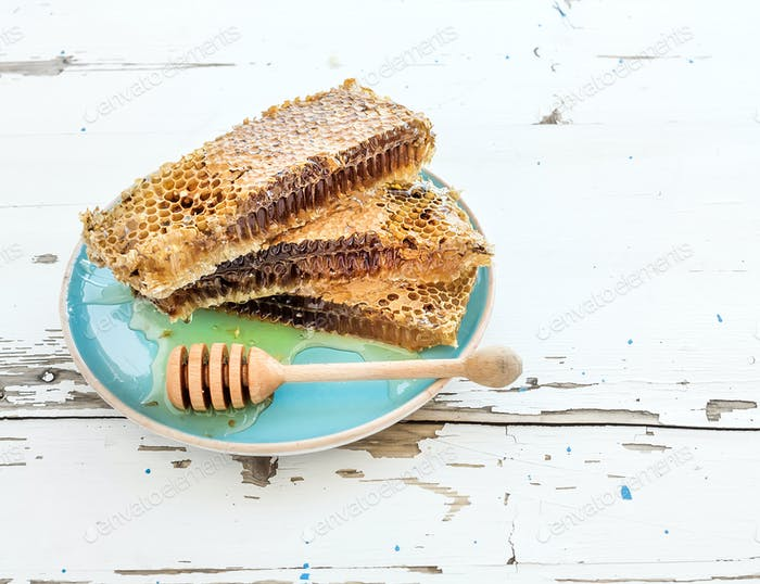 Honeycomb with honey dipper on blue ceramic plate over rustic white wooden table.