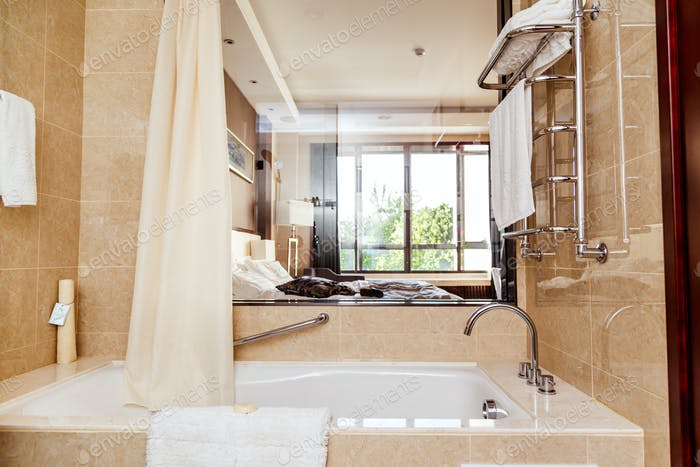 Hotel bathroom interior with window and bathtub.
