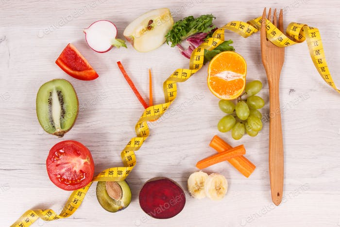 Tape measure with fruits and vegetables in shape of clock, healthy nutrition and slimming concept
