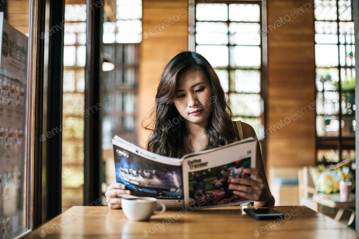 Beautiful woman reading magazine in cafe