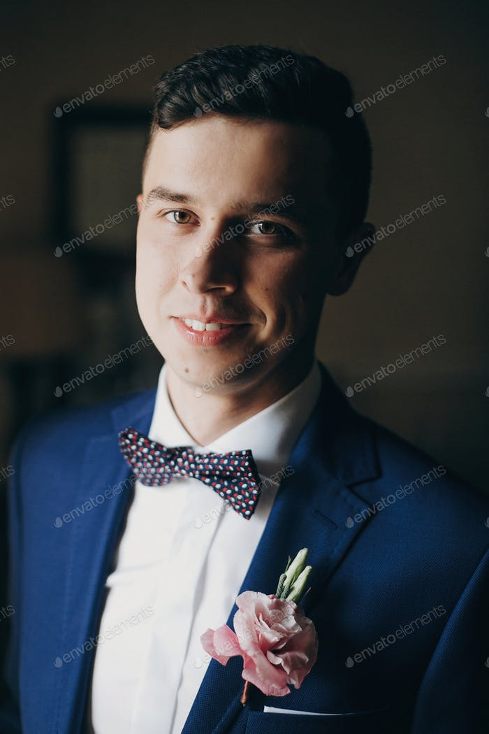 Stylish happy groom in blue suit posing and smiling near window