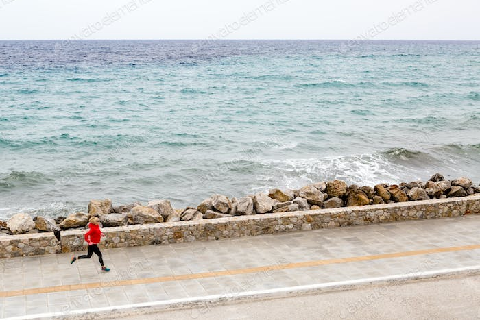 Woman jogging on city street at seaside