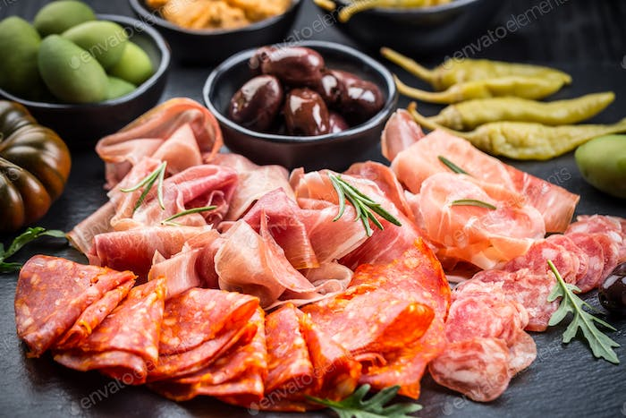 Platter of antipasti with a mixture of salami, prosciutto, bocconcini, peppers, tomatoes and olives