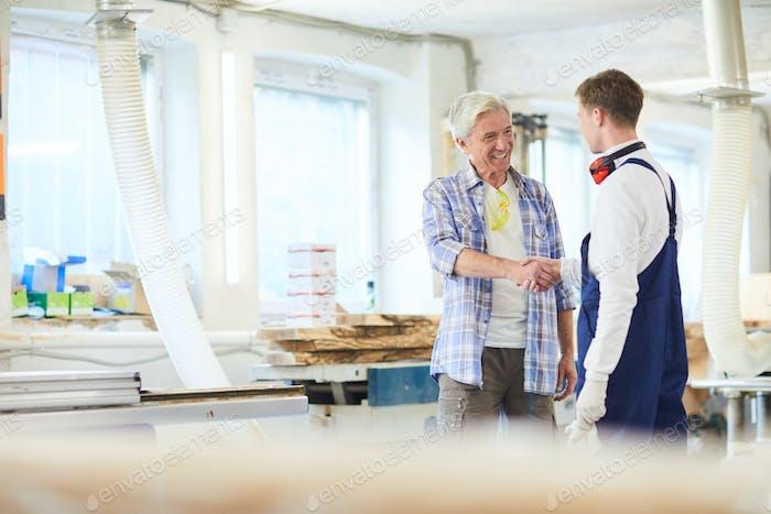 Carpentry workers shaking hands in woodworking studio