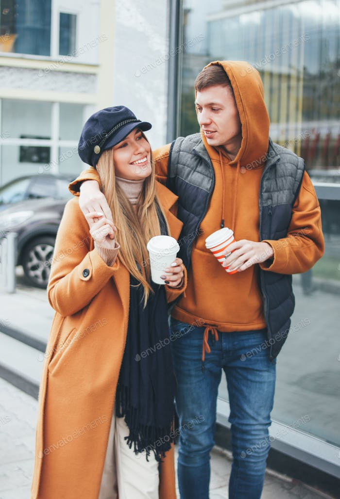 Happy young couple in love friends dressed in casual style walking on city street in cold season
