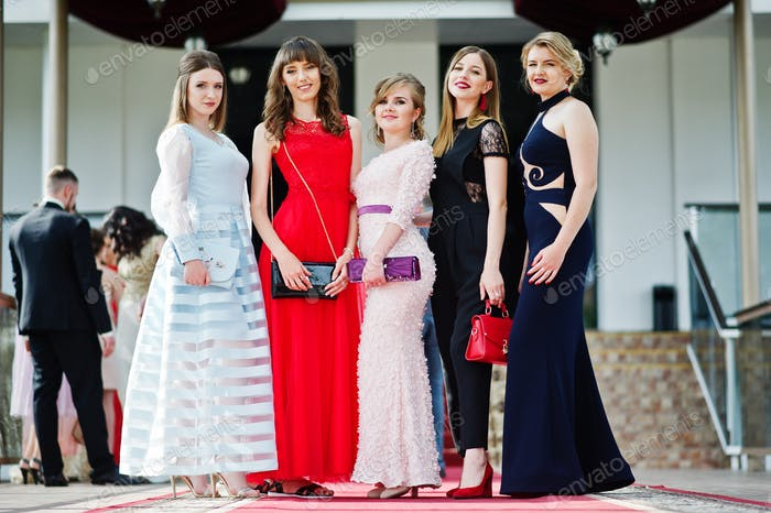 Fantastic young women in awesome fashionable dresses posing in the restaurant.