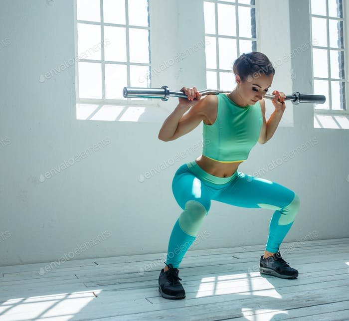 A woman squatting with barbell.