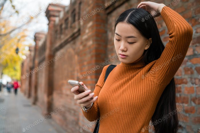 Asian woman using her mobile phone.