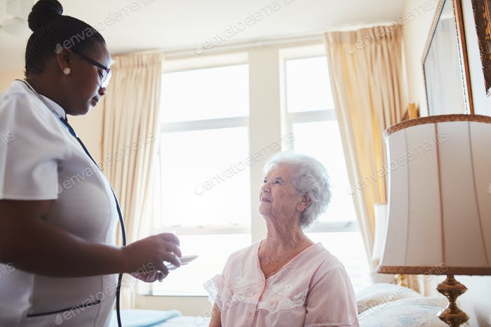 Female nurse assists an elderly female patient with medicines
