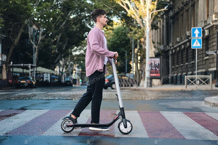 Side view of young man with e-scooter going on pedestrian crossing on city street