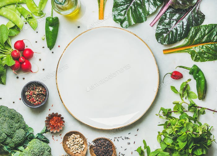 Fresh greens, vegetables and grains with white plate in center