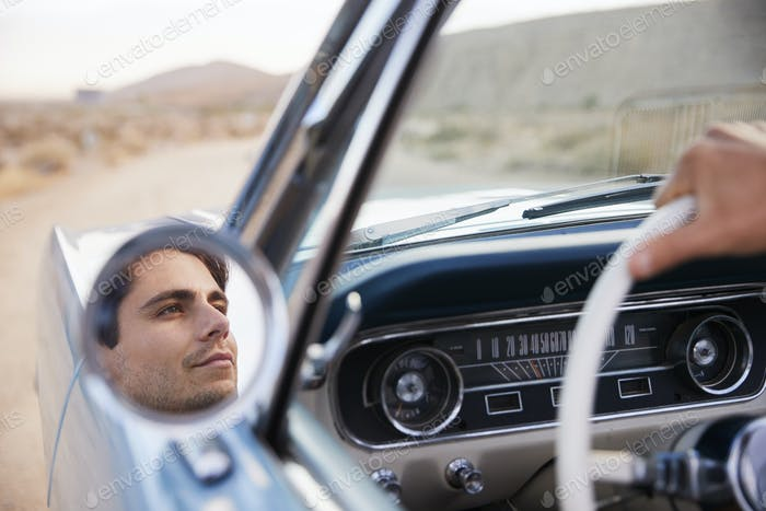 Man On Road Trip Driving Classic Convertible Car Reflected In Wing Mirror