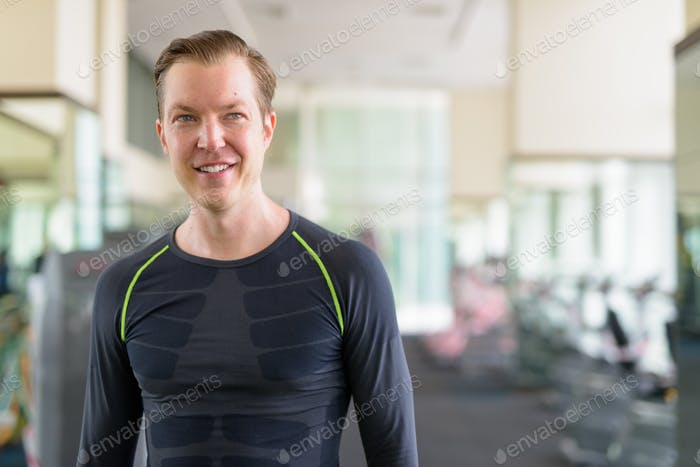 Portrait of happy young handsome man thinking at the gym during covid-19