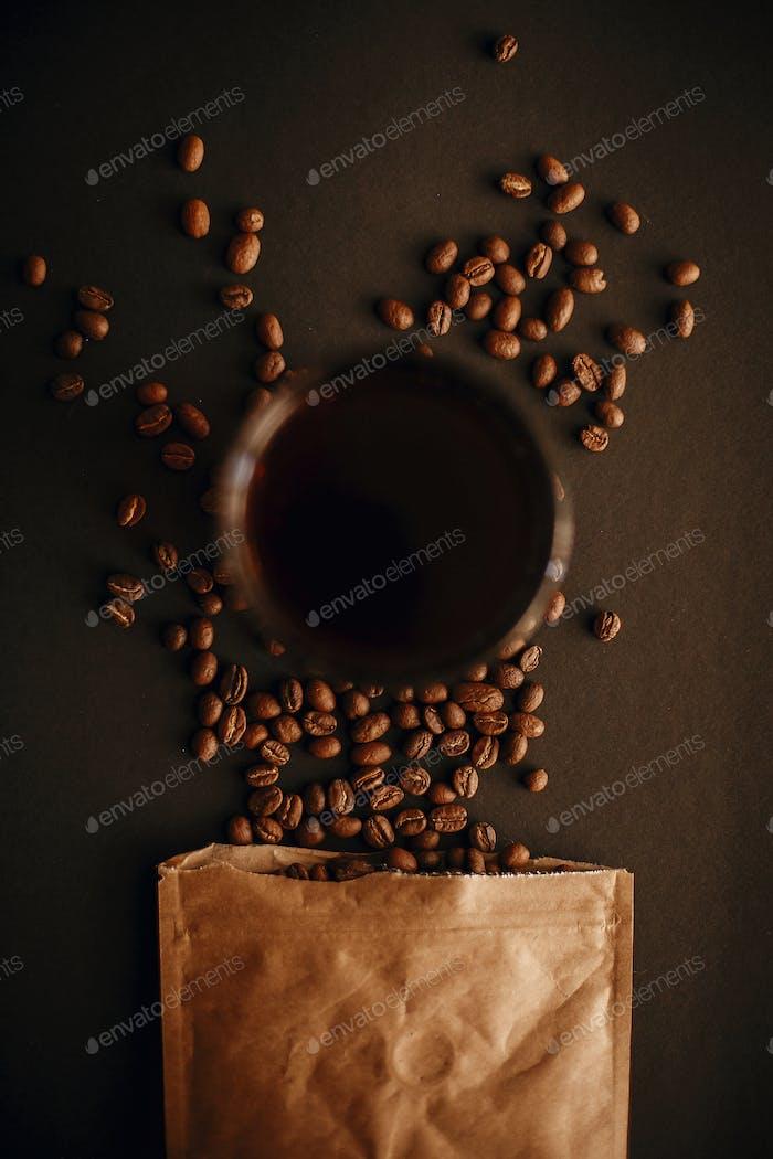 Kaffee in Glasbecher und Kaffeebohnen aus Papierpackung verstreut