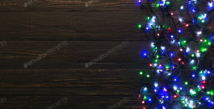 Colorful christmas lights on dark wooden background