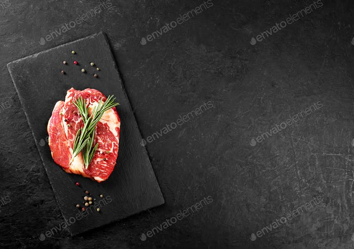 Beef steak with rosemary and pepper on a black background