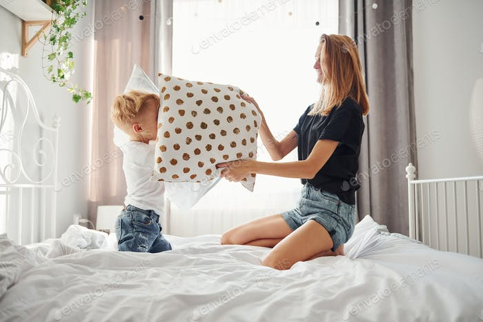 Mother playing pillow fight with her son in bedroom at daytime