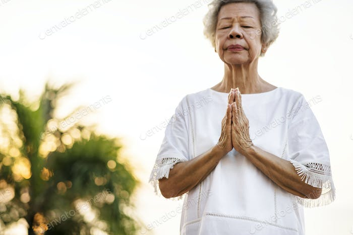 Senior woman practicing yoga in the morning